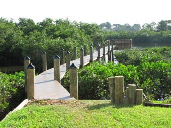 New Azek Dock on Anclote River with bollard poles, black cone caps, and bench.